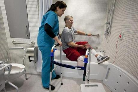 Occupational therapist Marissa Osborne helped Marathon bombing victim J.P. Norden of Stoneham practice getting in and out of a bathtub with a seat at the Spaulding Rehabilitation Hospital in Charlestown.