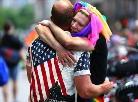 Friends Brandon Piatt (left) and Patrick Vilella embraced before Piatt got on his motorcycle to ride in the parade. Scores of political candidates also marched the parade.