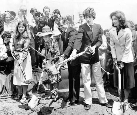 June 12, 1977:  Three generations of Kennedys dug small scoops of muddy soil during groundbreaking ceremonies for the John F. Kennedy Library construction at the University of Massachusetts Harbor Campus. From left, Caroline Kennedy, Rose Kennedy, Sen. Edward Kennedy, John Kennedy Jr. and Jacqueline Kennedy Onassis do the ceremonial honors. Sen. Edward Kennedy marked the day by saying,