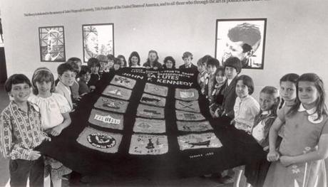 June 12, 1980: Fourth graders from Lexington's Fiske School display a 6-by-10 foot quilt they made and presented to the John F. Kennedy Library. The children began work on the green banner, which bore patches representing quotations from the late president and scenes from his life, about four months before. Teacher Nancy Tokarz supervised the project.