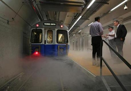 Smoke surrounded a subway car during a fire simulation as the MBTA previewed its new, state-of-the-art underground emergency training center in South Boston. Among officials attending were, from left, Randy Clarke, the MBTA's senior director of security and emergency management, MBTA Transit Police Chief Paul MacMillan, and Boston Fire Commissioner Roderick J Fraser Jr.