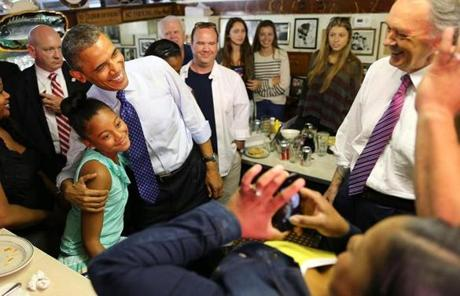 President Obama posed with Leilani Guthrie, 11, of Boston as her parents, Natalie and Sean, took a photo and Representative Ed Markey looked on at Charlie's Sandwich Shoppe in the South End. Obama visited Boston to campaign for Markey for US Senate.