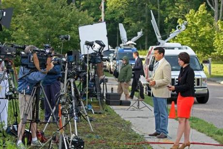 Television reporters gave broadcast reports on Hernandez's street.