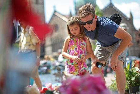 Ava Bowman, 5, and her father, Brooks, of Los Angeles, paid their respects at the Boston Marathon bombing memorial in Copley Square a few days before the items placed there were moved to the City Archives.
