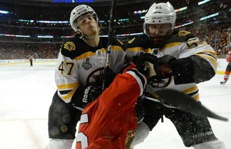 Torey Krug (left) and Johnny Boychuk (right) checked Andrew Shaw.