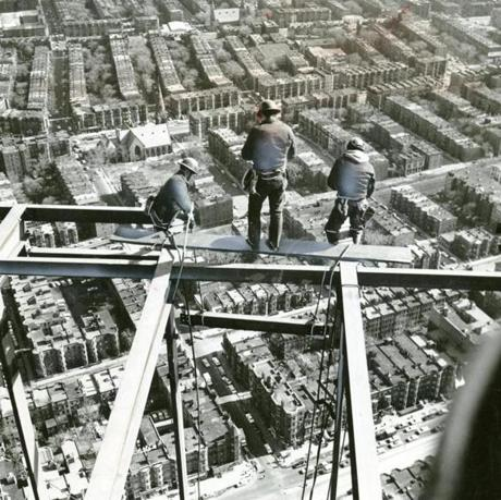 May 7, 1963: These steel workers paid strict attention to their task of putting finishing touches on the Prudential Tower. The workmen are perched perched more than an eighth of a mile in the air as they worked a beam into position. A skyview restaurant was included in the plans for the top of the Back Bay building.