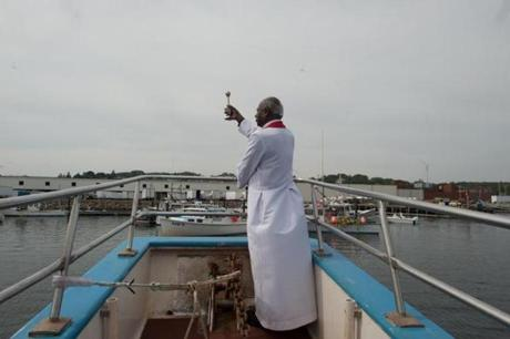 The Rev. Linus Mendis of Holy Family Parish, Gloucester, blessed the boats on the last day of the annual St. Peter's Fiesta.