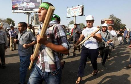 Egyptian men supporting President Morsi wielded weapons while gathering in a rally in Cairo.