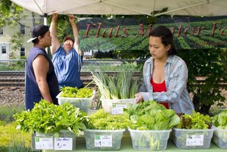 Yin Ly Hang (rear) with her children Sunny (left) and Mairi of Flats Mentor Farm at the Ashland farmers' market.