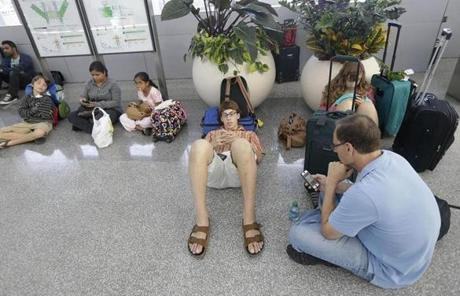 Bob Merberg (foreground) sat with his two children after their flight to Rochester, N.Y., was canceled.