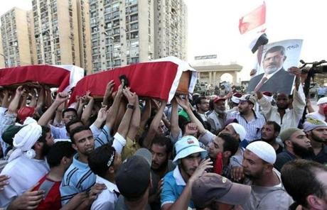 Mock coffins were carried in a symbolic funeral for the four men killed during Friday's clashes.