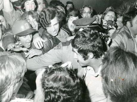 October 8 1975 / fromthearchive / Globe Staff photo by Dan Sheehan / Red Sox centerfielder Fred Lynn gets the attention of the the celebratory crowd gathered at Logan airport for the team arrival at 7:30 am. He got help from a State Policeman as he wended his way through the fans who welcomed home the team home after they won their first American League pennant in 8 years. Fred Lynn won both the American League Rookie of the Year award and the Most Valuable Player, a feat which had never previously been accomplished.