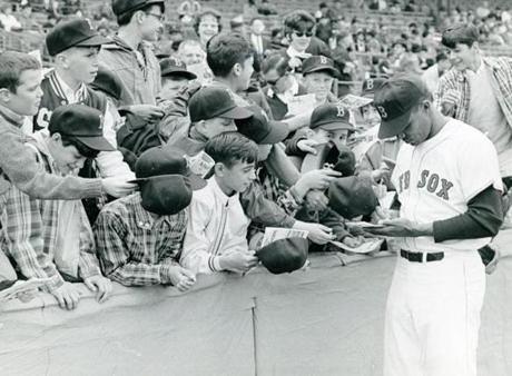 May 22 1966 / fromthearchive / Globe Staff photo by Dan Goshtigian / Red Sox pitcher Earl Wilson signs autographs for young fans at the annual Globe-Red Sox baseball clinic. Over 4000 youngsters watched manager Billy Herman run a group of his players through drills to the delight of the young fans who ranged in age from little leaguers to high school players. Then Earl Wilson, Ken Sanders and Jose Santiago moved out to the bullpen and talked to those youngsters interested in pitching and catching.