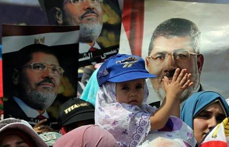 A baby latched onto a poster of ousted Egyptian President Mohammed Morsi during a protest Tuesday in Cairo.