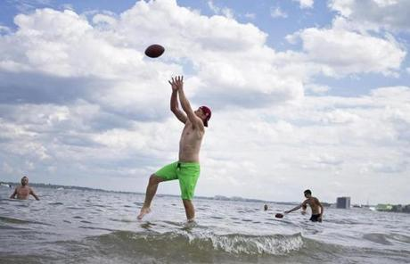 Craig Dwyer of Boston caught a pass from Greg Berman, not pictured, at Carson Beach in South Boston, where they went to escape the week's long heat wave.