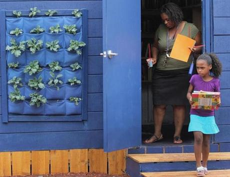 Dorchester, MA 071313 Nola Hood (cq) and niece, Laila Hood (cq), 6, left a book swap during the kick-off of Bowdoin-Geneva Community Hub in Dorchester, Saturday, July 13 2013. (Staff Photo/Wendy Maeda) section: Metro slug: market reporter: Akilah Johnson