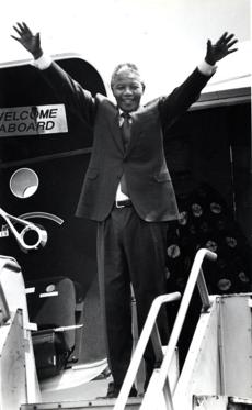 June 24 1990 / fromthearchive / Globe Staff photo by Jonathan Wiggs / Nelson Mandela waved goodbye to Boston from the 727 airplane doorway. Mandela's six-week, 13-nation tour was designed to raise awareness of the antiapartheid struggle of South African blacks and to raise money for the African National Congress. It was the black leader's first visit to the United States since he was freed in February after 27 years as a political prisoner in South Africa. Boston was Mandela's second stop after New York and more than $ 500,000 in contributions were raised here for the ANC.