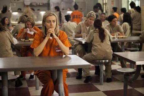 "Taylor Schilling sits in what Piper Kerman calls the ""chow hall,"" in the  Netflix series based on Kerman's prison term."