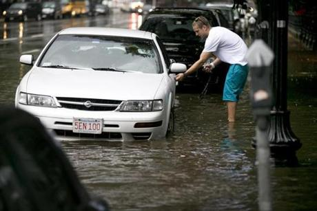 Evan Arvedon of Foxborough returned to his car, which fortunately started, after a flash flood on Charles Street between Boston Common and the Public Garden during a heavy rainstorm.
