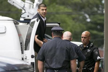 Former Patriots player Aaron Hernandez exited a police van to enter Attleboro District Court for a probable cause hearing, which was postponed, in the murder of Odin Lloyd.