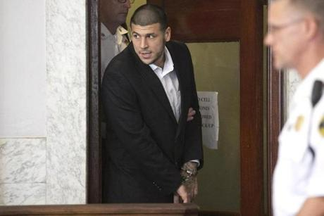 Aaron Hernandez entered Attleboro District Court for a probable cause hearing in his murder case. A judge delayed proceedings until Aug. 22 after prosecutors asked for more time to prepare.