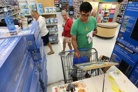 Teri Murphy (left) and Roberta Case of Quincy watched as Brendan O'Connell created his art at the Quincy Walmart.