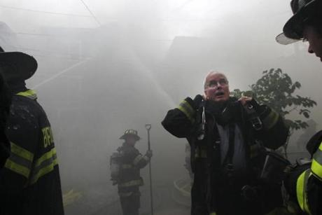 A firefighter put on an oxygen tank as multiple fire departments responded to a seven-alarm fire on Calvin Street in Somerville.