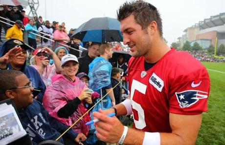 Tim Tebow signed autographs for fans.