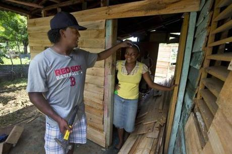 El Mamon, Dominican Republic- Globe Staff Photo by Stan Grossfeld---Pedro Martinez removes some sawdust from the hair of Diosmery Rosario Arias whose mother's home is being rebuilt as part of the Lindos Suenos Beautiful Dreams, program near the Red Sox Academy.