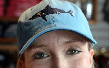 Sara Handler, inventory manager at Chatham Clothing Bar, models one of the store's popular hats. Worldwide, shark tourism generates as much as $314 million a year, according to one recent study.