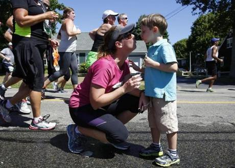 Brady Lewis, 4, of Houston, Texas (R) kisses his mom, Amanda, as she stops running to greet him during the Falmouth Road Race in Falmouth, Massachusetts August 11, 2013. (Jessica Rinaldi For The Boston Globe)