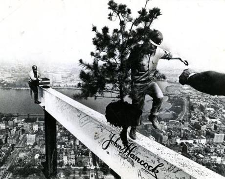September 27, 1971: A construction worker retrieved the fir tree after it was hoisted with the last girder in traditional topping-off ceremonies at the John Hancock Tower. The white-colored beam hoisted to the top and representing the final piece of structural steel to go into the construction of the building carried with it the American flag as well as the fir tree and signatures of many home office employees,  tree and signatures of many home office employees, construction workers and dignitaries. The 790-foot-high tower was now officially New England's tallest structure.