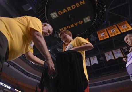 Boston, MA 081313 TD Garden usher Jim Borden (cq) (left) takes a backpack from Harrison Latimer (cq), 11, (son of Amy Latimer (Cq) TD Garden President) Salvation Army and TD Garden volunteers help fill up back-packs for Back to School Garden Neighborhood Chariites and the City of Boston. They were filling up back pack with back to school items on August 13, 2013. (Essdras M Suarez/ Globe Staff)/ MET
