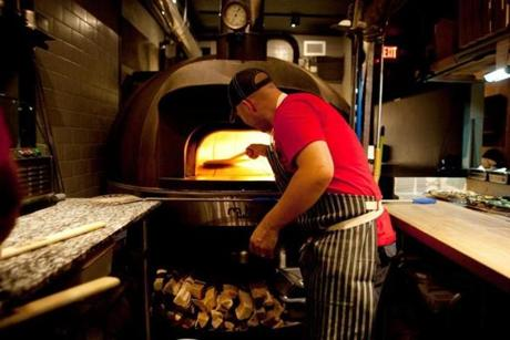 A pizza is placed inside the oven at A4 in Somerville.