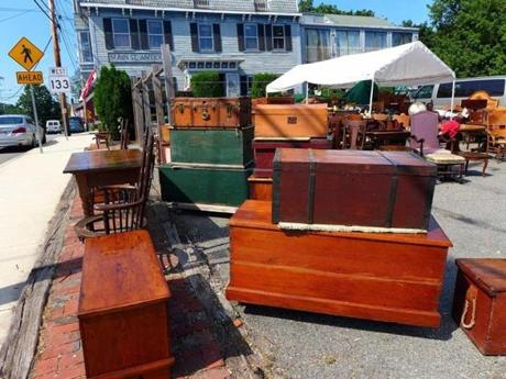 Old chests and trunks from Main Street Antiques are displayed in the parking lot.