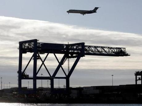 A plane approached Logan Airport above the cranes at Conley Terminal.