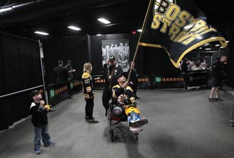 Marc practiced waving the Boston Strong flag with his son and fiancee before going on the ice before a Bruins game.