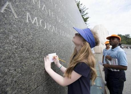 Brianna Renner, 11, left, and Morgan Koroma, 11, both from Cora Rich Elementary School in Prince Georges County, Md., read and write down quotes from Martin Luther King's speeches and writings, inscribed on the wall at the Martin Luther King Memorial in Washington, Wednesday, Aug. 28, 2013, during the Let Freedom Ring ceremony commemorating the 50th Anniversary of the March on Washington for Jobs and Freedom. Renner, a sixth grader, said that they are writing the quotes that they'll discuss in their Social Studies class, and pick which one they think is one that stands out most. (AP Photo/Manuel Balce Ceneta)