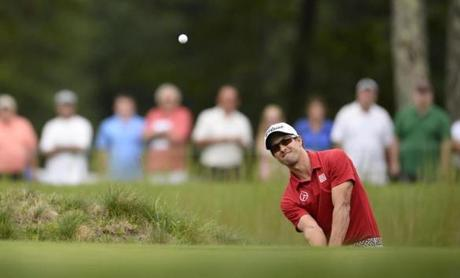Masters champion Adam Scott escapes from a bunker on the 14th hole. He would shoot a 73.