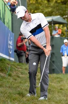Rory McIlroy chips from the rough onto the ninth green.