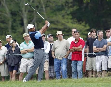 Tiger Woods holds his follow-through high as he hits out of the rough on No. 13.