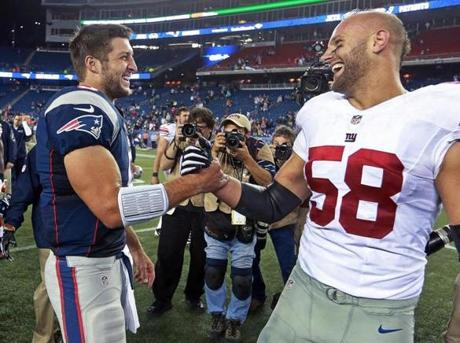 Tebow and former Boston College linebacker Mark Herzlich, now with the Giants, were all smiles after the game.