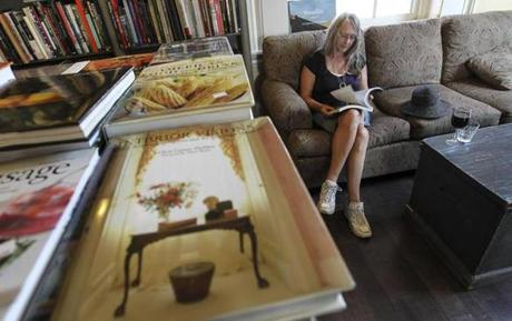 Elke Harrison of Ontario has a glass of wine as she reads at the Book & Bar in Portsmouth, N.H.