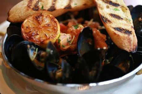 Mussels are served in a  broth of white wine and tomatoes with garlic and shallots.