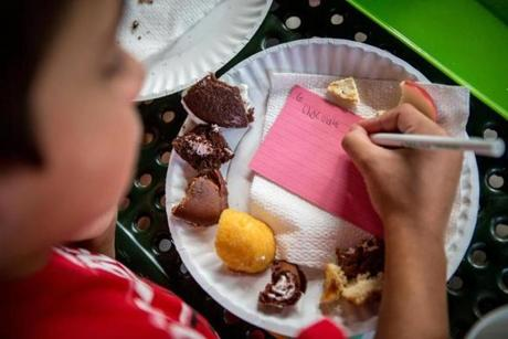 J.P. Riley, 10, marks his notecard during the snack cake sampling in Arsenal Park in Watertown.