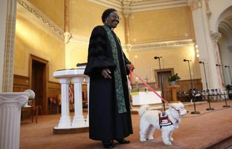 Reverend Tina Reid smiles from the altar with her service dog Franklin at Belmont A.M.E. Zion Church in Worcester, Massachusetts September 15, 2013. (Jessica Rinaldi For The Boston Globe)