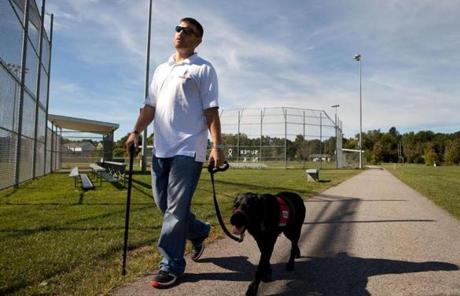 Kevin Lambert's service dog, a black Lab named Ronnie, helps the Army vet's  post traumatic stress disorder at bay.