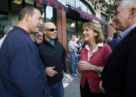 Martha Coakley greeted Jamie Berger (left) of Auburn and Tyler Castagno of Wayland outside Fenway Park, along with husband Thomas F. O'Connor Jr. The stop was the highlight of a campaign tour that took her through 19 communities.