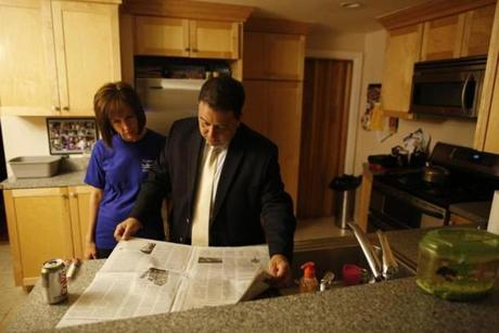 Rob Consalvo and his wife, Michelle, looked over the morning paper in their kitchen in Hyde Park, Massachusetts September 19, 2013. (Jessica Rinaldi For The Boston Globe)