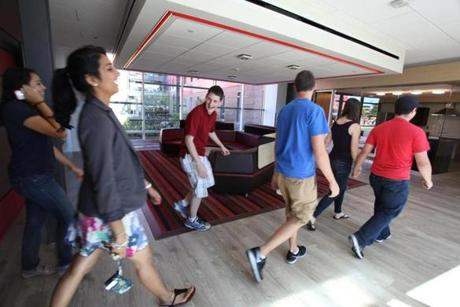 UMass-Lowell students walk through a common sitting area and kitchen.